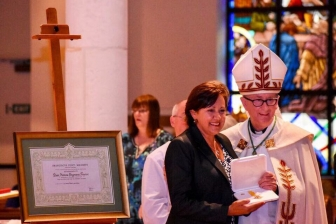 Andrea Krazeise, executive director of The Pregnancy Center of Sanford & Oviedo, accepts a medal and a document signed and sealed by Pope Francis.