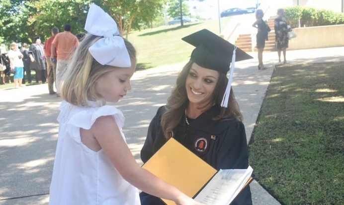 Shelby shows off her diploma to her 5-year-old daughter, Laura Leigh.